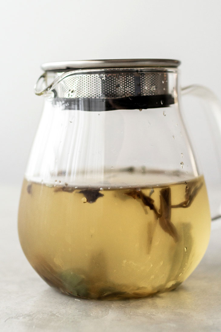 Steeping loose white tea in cold water in a glass teapot.