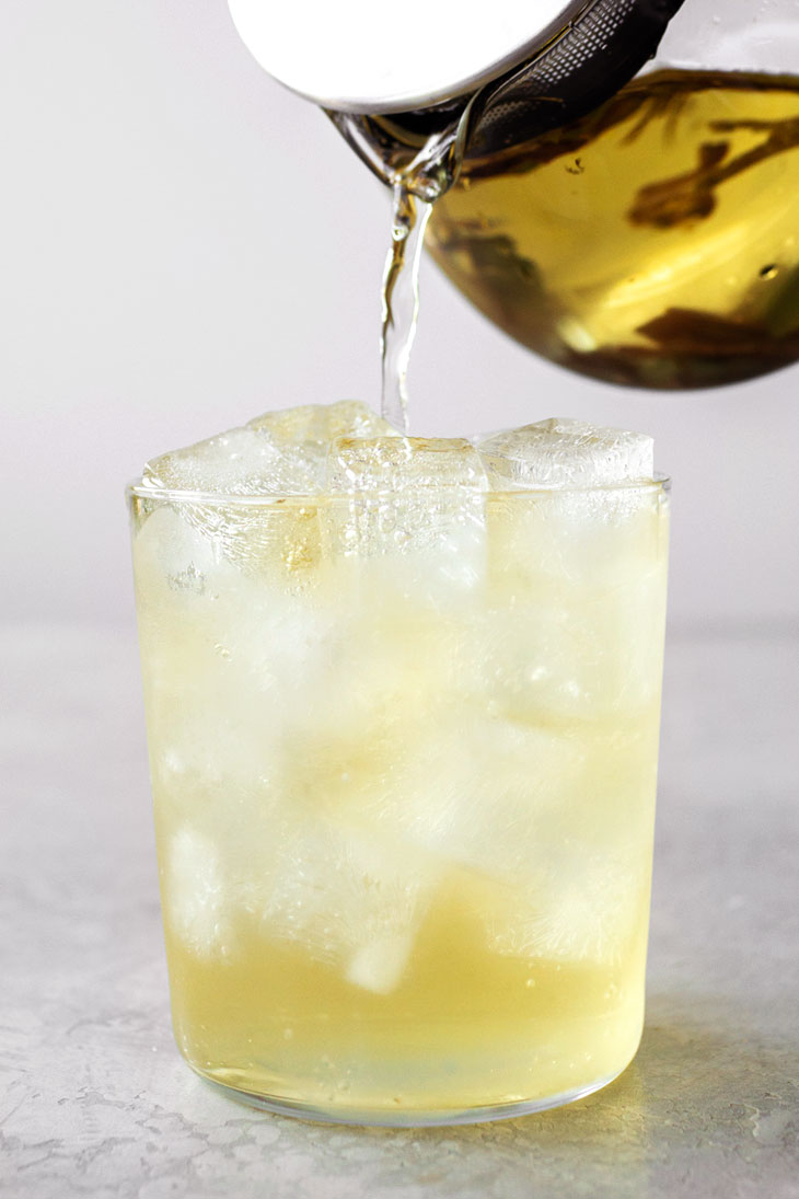 Pouring white tea into a glass filled with ice.
