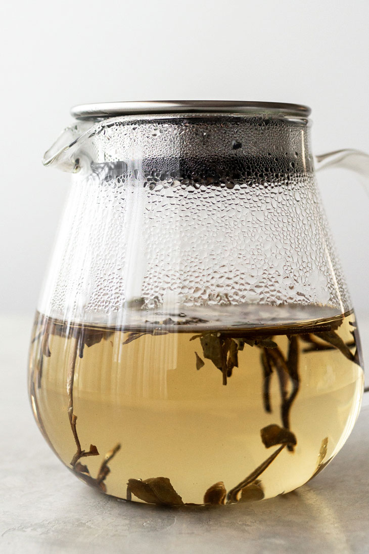 White peony tea steeping in a glass teapot.