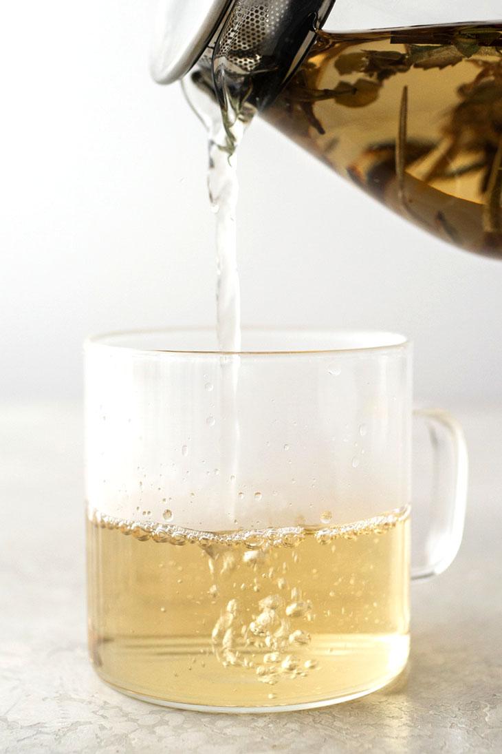 Pouring white peony tea into a glass mug from a teapot.