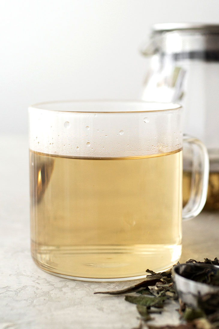 White tea in a glass mug with teapot in background.