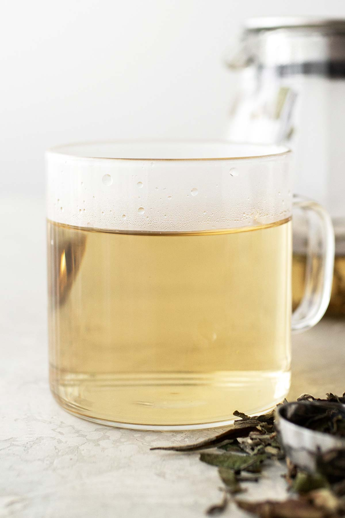 White Peony tea in a glass mug with teapot in background.